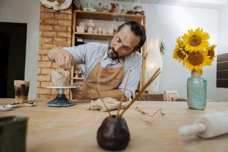 Das dunkelhaarige handicraftsman, das am Tisch mit Aroma arbeitet, haftet stockbild