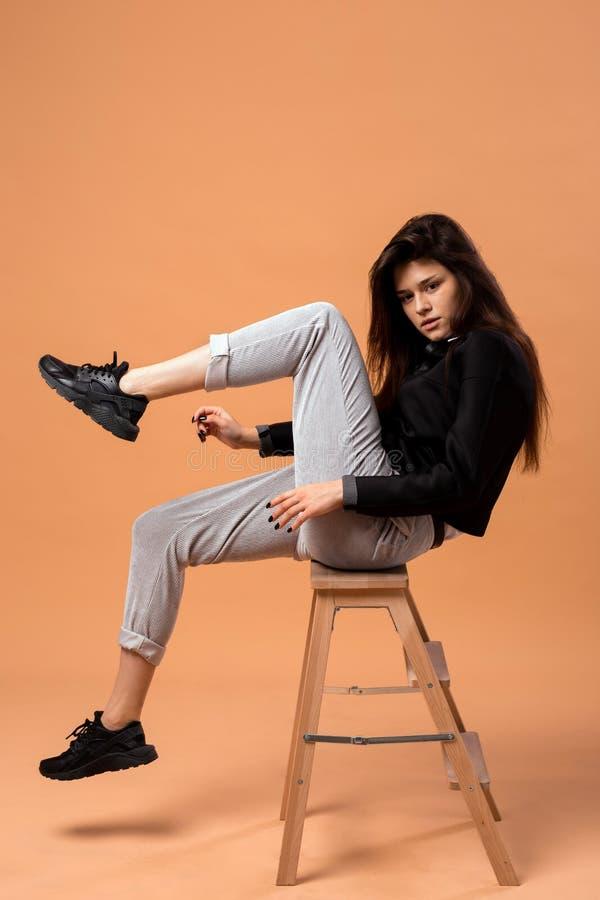 Das dunkelhaarige Mädchen, das im weißen Hemd, in der grauen Hose, in der schwarzen Jacke und in den schwarzen Turnschuhen geklei lizenzfreie stockfotos