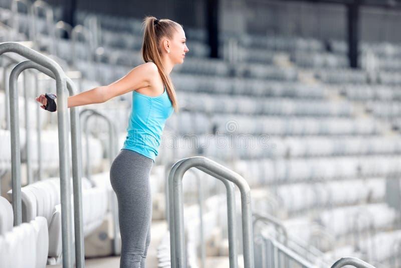 Das Eignungsmädchen, das Gymnastik ausdehnt und tut, trainiert auf Stadionstreppe Athletenmädchen und -leute, die Konzept ausarbe lizenzfreies stockbild