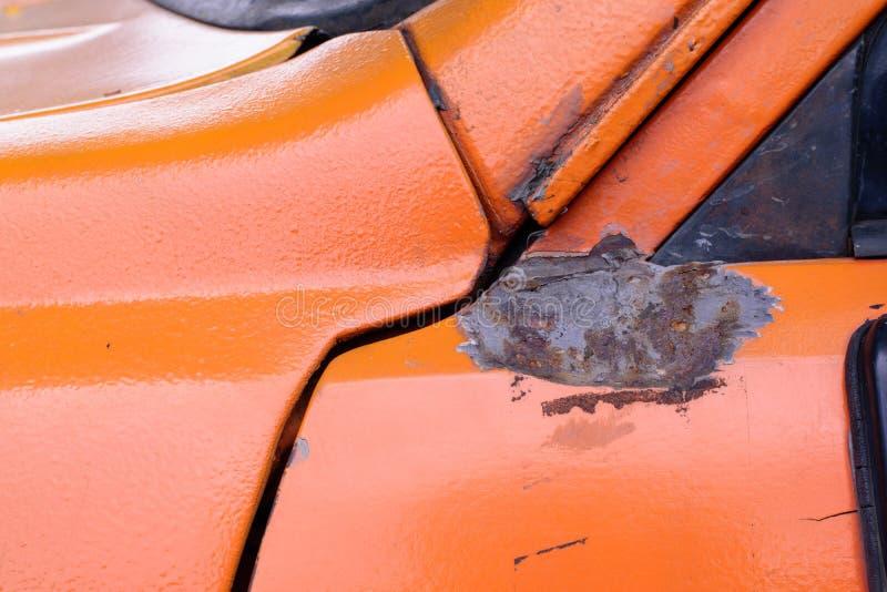 Das eingebeulte Auto auf der orange Oberfläche stockfotos