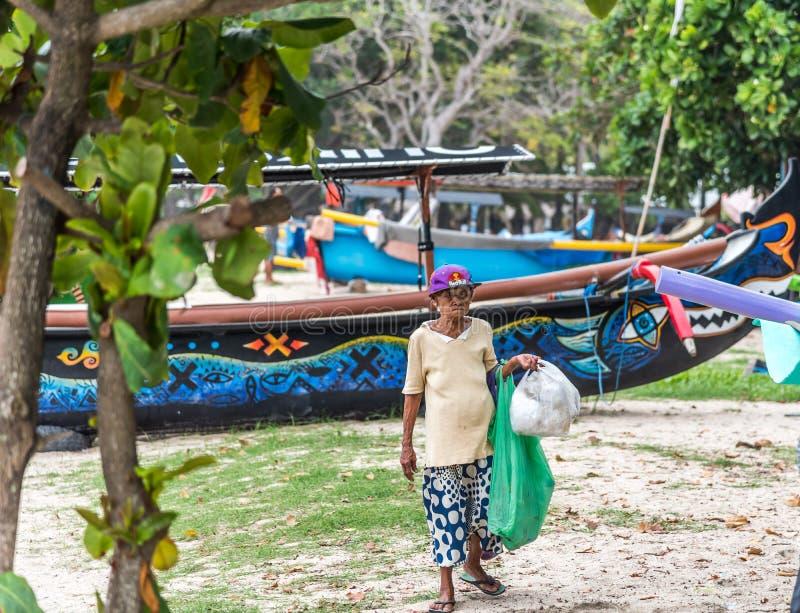Das Einheimische alterte weiblichen Balinese Abfall entlang dem Küstenvorland sammelnd stockbilder