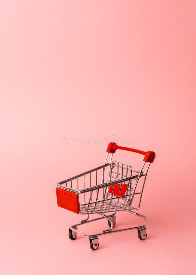 Das Einkaufen der Frauen: eine leere Miniaturlaufkatze von einem Supermarkt auf einem rosa Hintergrund stockfoto