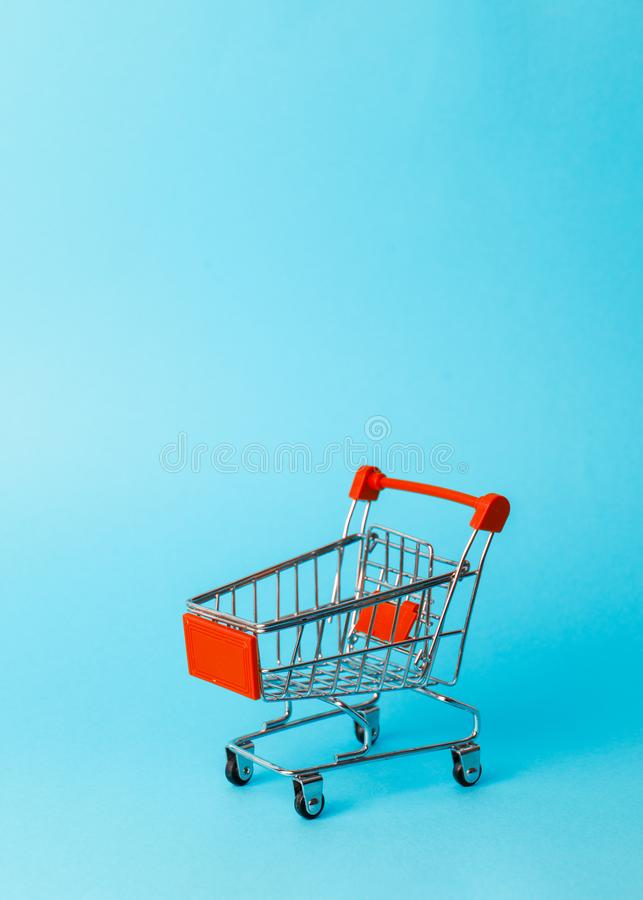 Das Einkaufen der Frauen: eine leere rote Miniaturlaufkatze von einem Supermarkt auf einem blauen Hintergrund stockfotografie