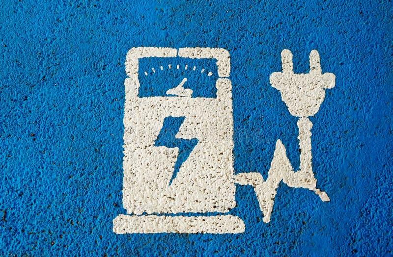 Das Elektro-Mobil, das allgemeines Stationszeichen auf Blau auflädt, malte Asphalt lizenzfreies stockfoto