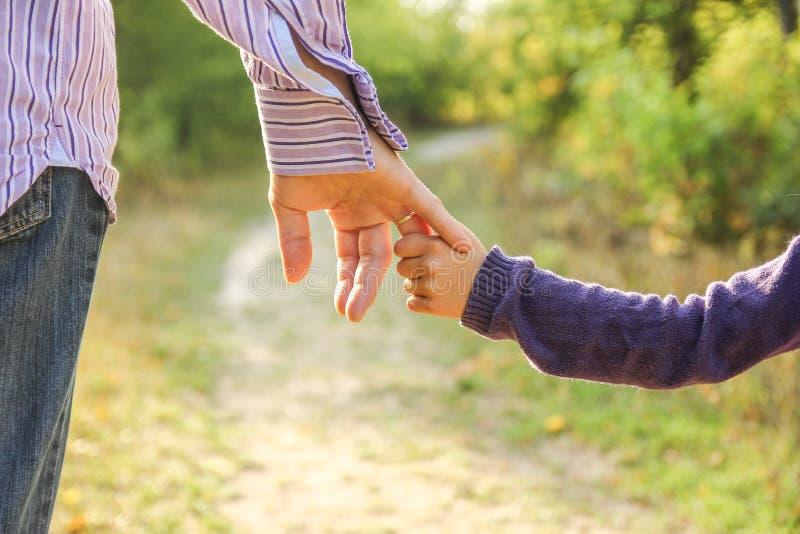 Das Elternteil, welches die Kind-` s Hand mit einem glücklichen Hintergrund hält stockbilder