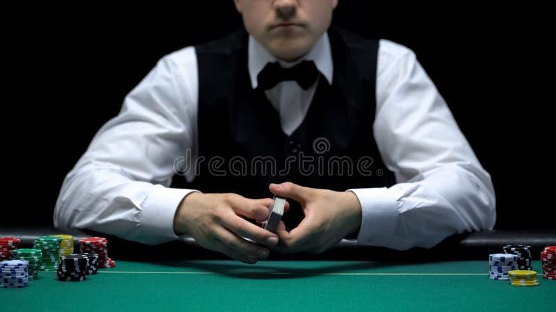 Das erfahrene Croupier, das Karten hält, bereiten für Pokerspiel am Kasino vor und spielen lizenzfreie stockbilder