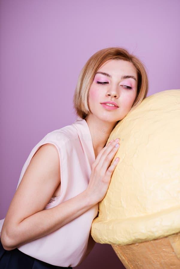 Das erstaunliche attraktive blonde Mädchen, das große Stützen hält, zacken Eiscreme aus lizenzfreie stockfotos