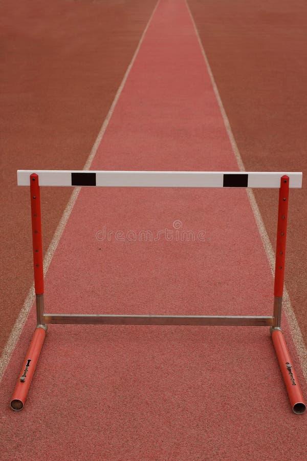 Das erste Hindernis Konzept mit einer Hürde auf roter Bahn lizenzfreies stockbild