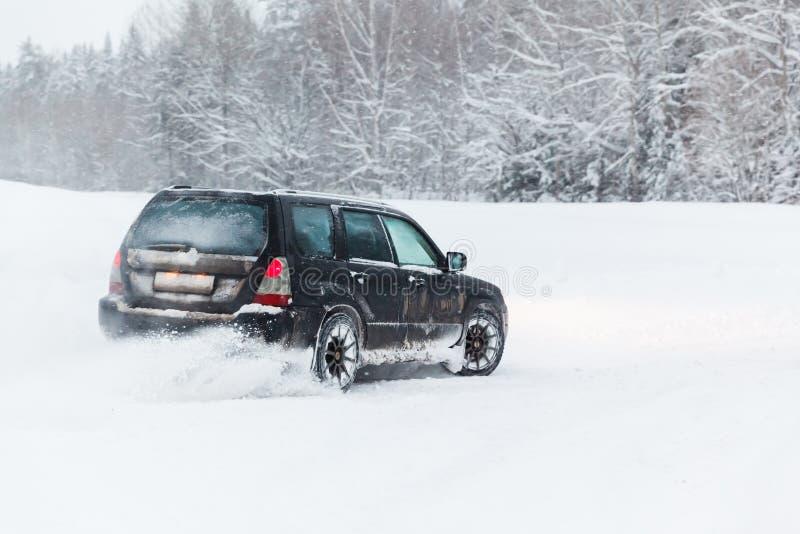 Das extreme Fahren, das Auto bewegt sich schnell über den glatten Schnee und stellt einen Spray des Schnees her lizenzfreie stockfotos