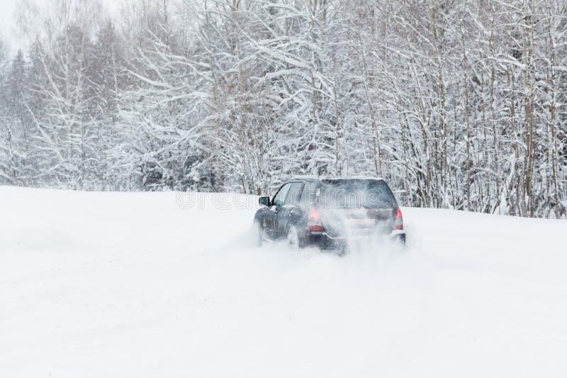 Das extreme Fahren, das Auto bewegt sich schnell über den glatten Schnee und stellt einen Spray des Schnees her stockbild
