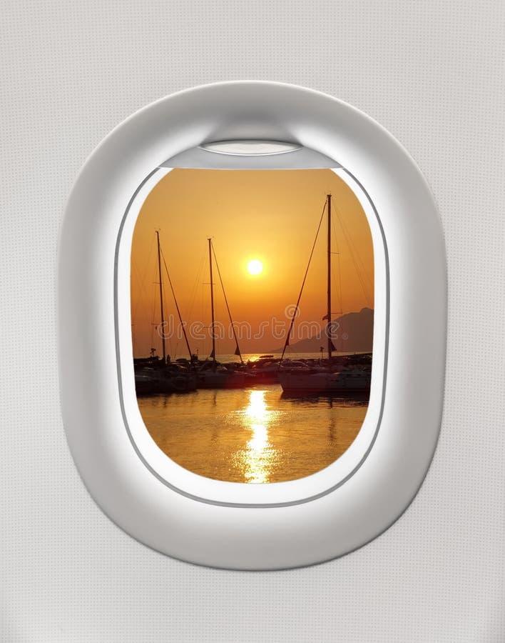 Das Fenster einer Fläche zum Sonnenuntergang im Hafen heraus schauen lizenzfreie stockbilder