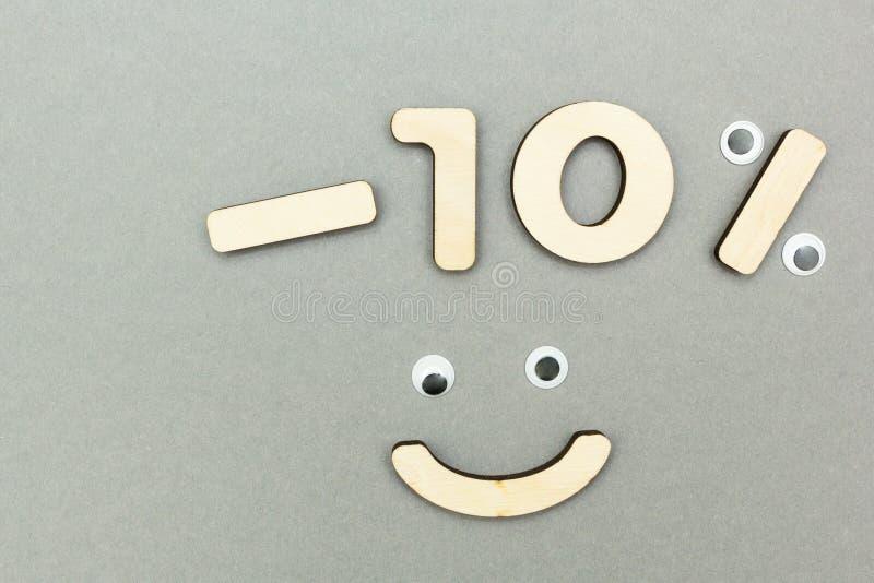 -10% das figuras de madeira em um fundo de papel cinzento smiley fotografia de stock royalty free