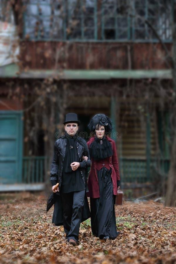 Das finstere Paar mit altmodischen Vampirbekleidung stockfotos