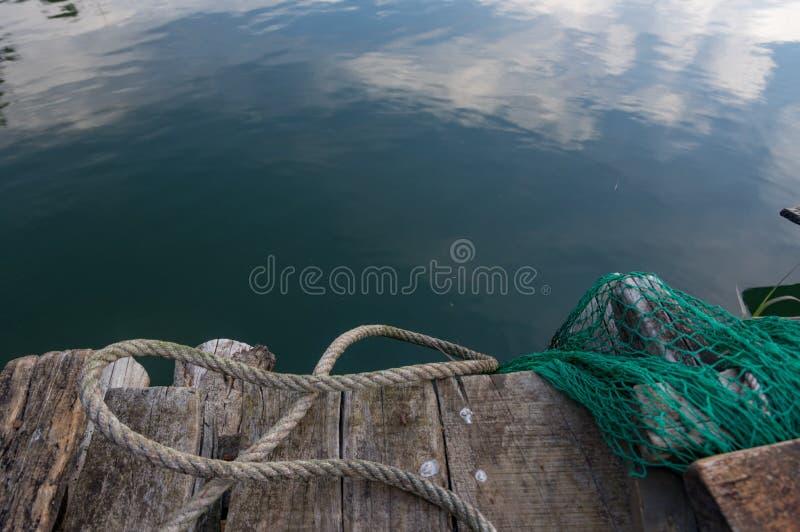 Das Fischenwerkzeug für Fischer auf dem See, dem Gitter und dem Kerl stockfotografie