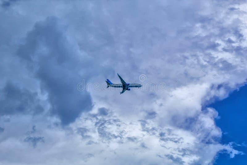 Das Flugzeug fliegt in den Himmel mit Wolken stockbild