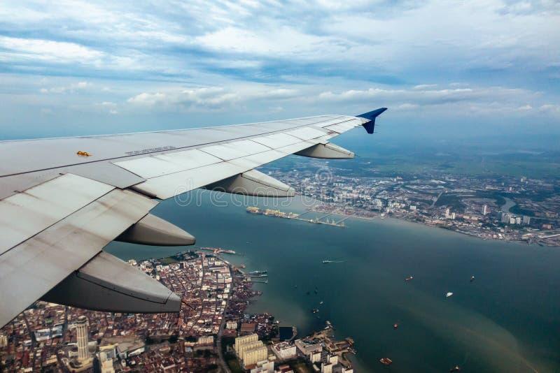 Das Flugzeug, das von Penang-Flughafen, ansehend vom Flugzeugfenster durch den Flügel sich entfernt, decken Penang von oben auf stockbild