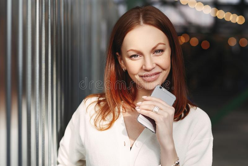 Das Foto der attraktiven jungen europäischen Frau mit erfülltem Ausdruck, gekleidet in der weißen Kleidung, hält intelligentes Te stockfoto