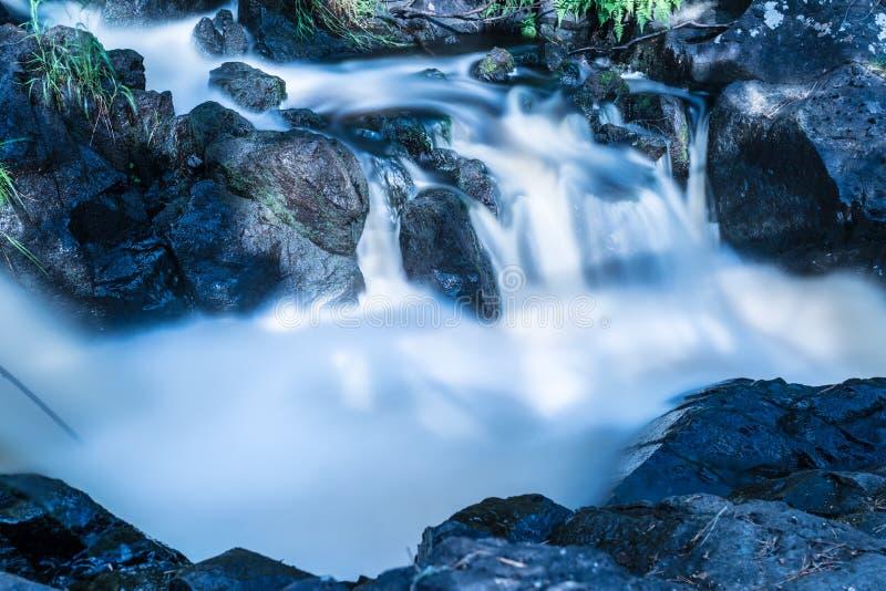 Das Foto des kleinen Wasserfalls oder des Katarakts im Wald taked am warmen sonnigen Sommertag mit der langen Belichtung lizenzfreies stockbild