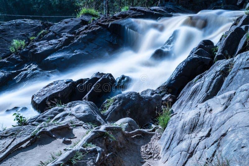 Das Foto des kleinen Wasserfalls oder des Katarakts im Wald taked am warmen sonnigen Sommertag mit der langen Belichtung lizenzfreies stockfoto