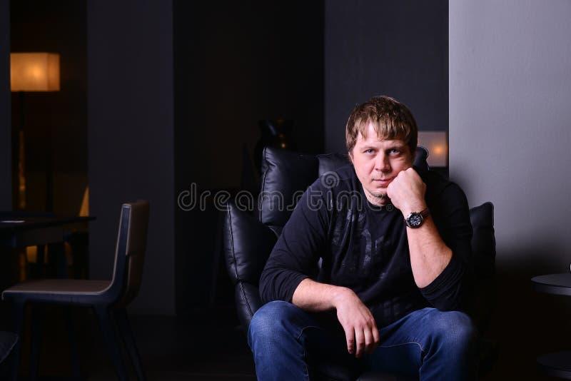 Das Foto, das vom Mann sitzt Innen ist nachdenklich, in einem Ledersessel lizenzfreies stockfoto