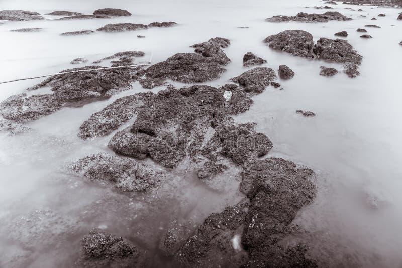 Das Foto, das von den langen Belichtungs-Fotografie-Wellen auf Steinstrandwasser Schwarzweiss ist, umranden abstrakten Seehinterg lizenzfreie stockfotografie