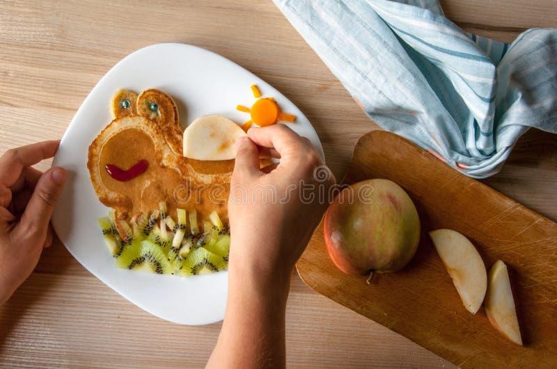 Das Frühstück der lustige Kinder: Pfannkuchen lizenzfreie stockfotografie