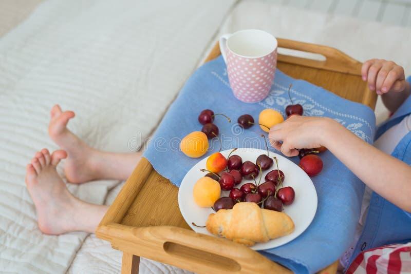 Das Frühstück des Kindes auf einem Bett stockfotos