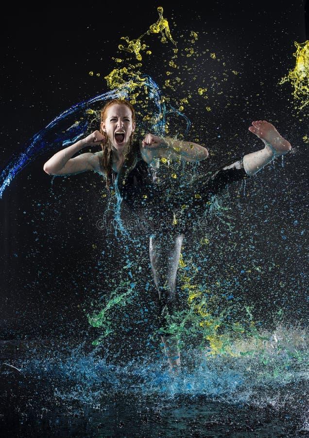 Das Frauen-hohe Treten in buntes Wasser spritzt stockfoto