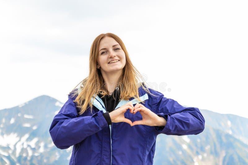 Das Frauengefühl, das glücklich ist, eine Herzform mit ihren Händen gegen auf Gebirgsfelsen machend landschaftlich, gestalten stockbild