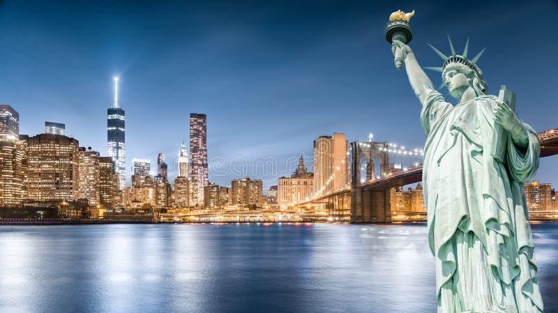 Das Freiheitsstatue mit Brooklyn-Brücken- und Lower Manhattan-Hintergrund am Abend, Marksteine von New York City stockbilder