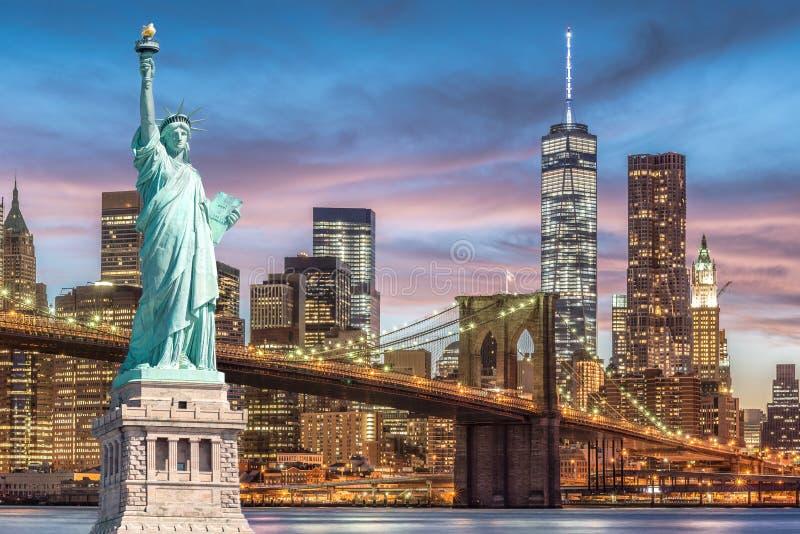 Das Freiheitsstatue und Brooklyn-Brücke mit World Trade Center-Hintergrunddämmerungs-Sonnenuntergangansicht, Marksteine von New Y lizenzfreie stockfotografie