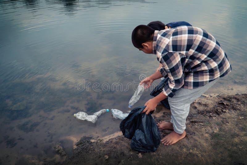 Das freiwillige Sammeln oben ein Flaschenplastik im Fluss stockfotos