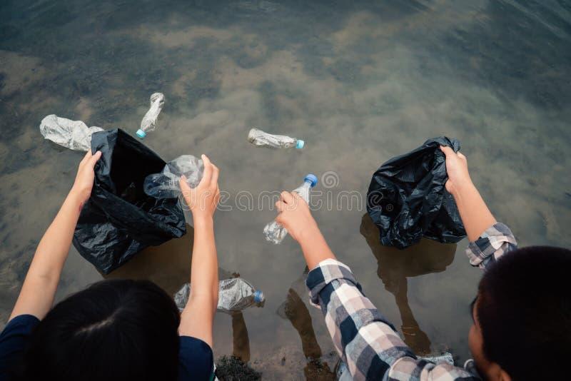 Das freiwillige Sammeln oben ein Flaschenplastik im Fluss stockbilder