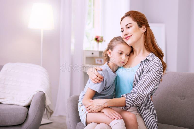 Das freudlose junge Mädchen, das auf ihren Müttern sitzt, hüllt ein stockfoto