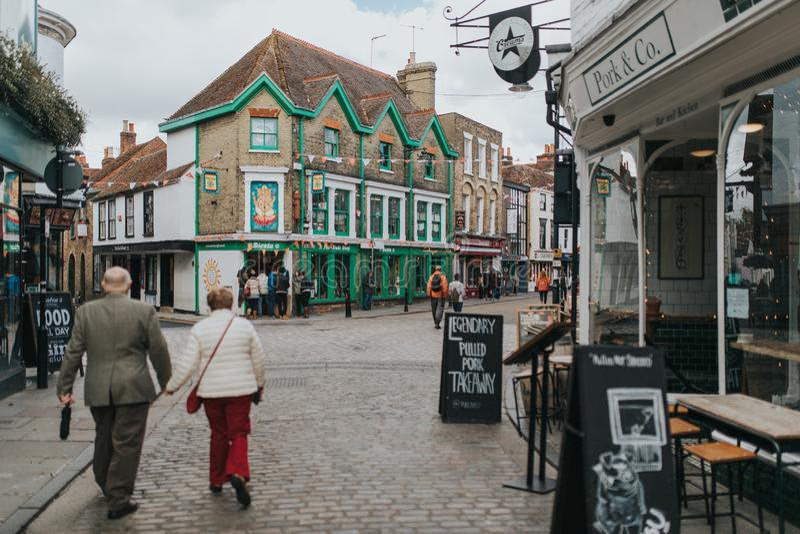 Das Fußgängergehen entlang cobblestoned Straße, mit kauft um es und traditionelle Architektur im Dorf von Canterbury, stockfoto