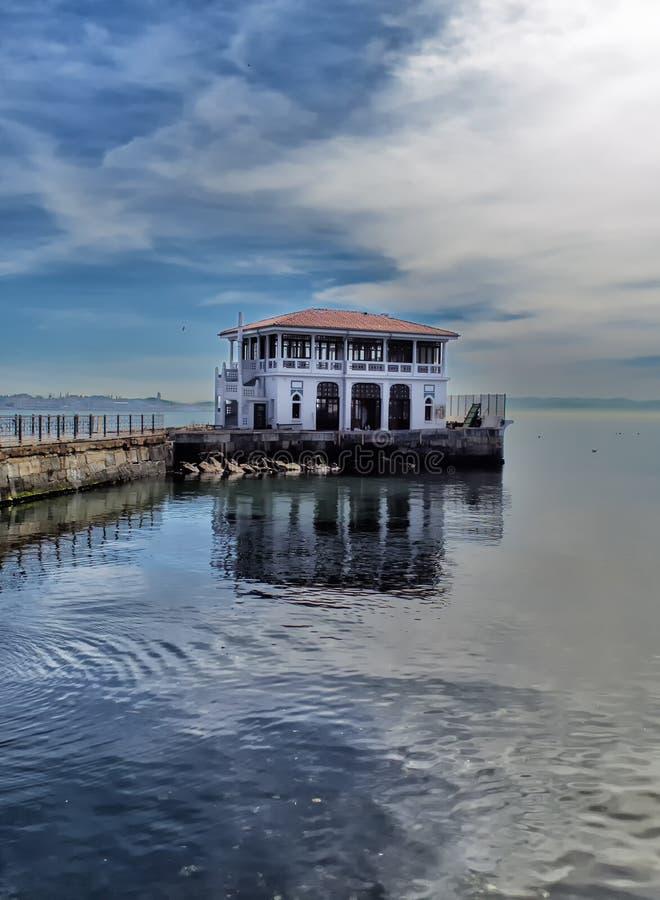 Das Gebäude eines Hafens für Schiffe für Stadttransport in Istanula in einem Stadtteil nannte Moda und seine Reflexionen auf d lizenzfreies stockfoto