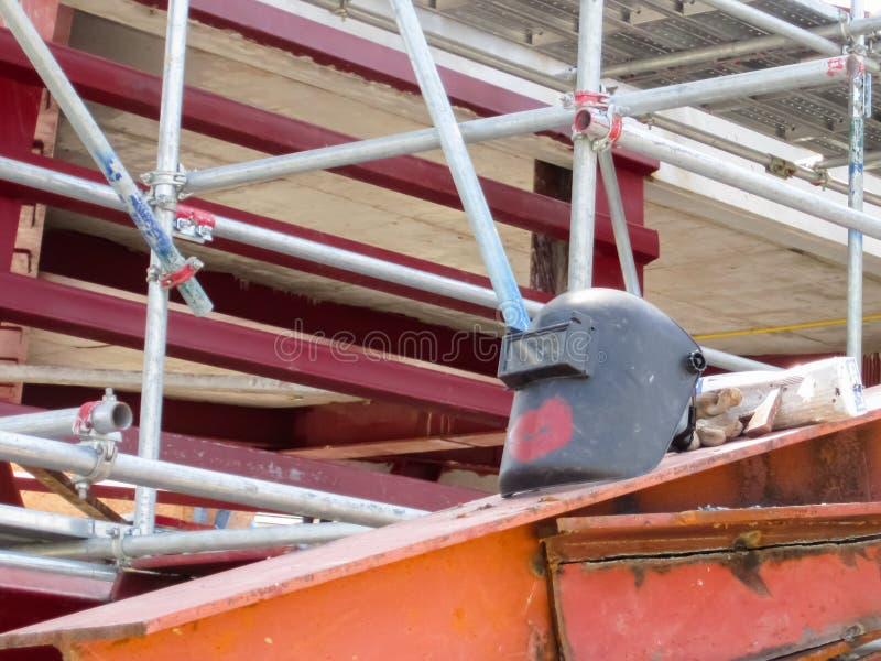Das Gebäude ist, ein schweißender Sturzhelm auf Dachstahl im Bau lizenzfreie stockbilder