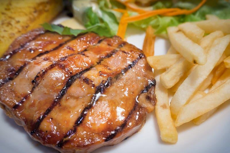 Das gegrillte Schweinekotelettsteak auf weißem Plattenabschluß herauf Bild stockbild