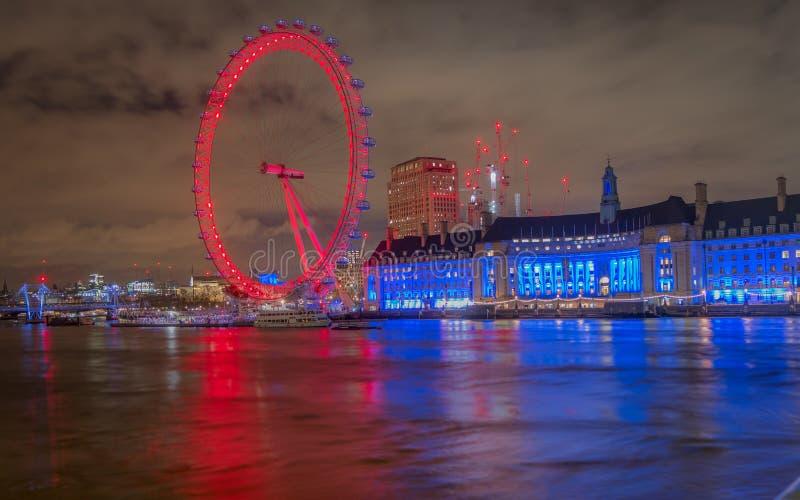 Das Genießen einer reizenden Ansicht des London-Auges beleuchtete mit bunten Lichtern nachts von der Westminster-Brücke stockbilder