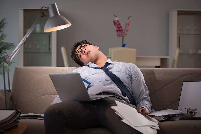 Das Geschäftsmannworkaholic, das spät zu Hause arbeitet lizenzfreies stockbild
