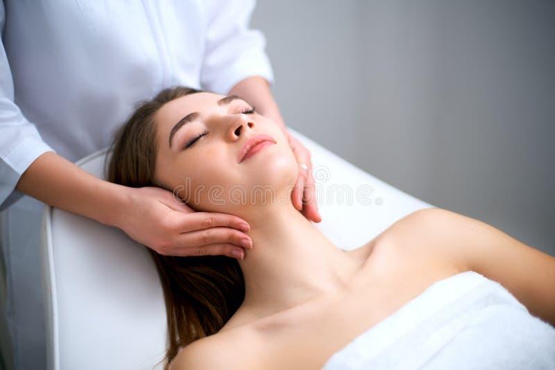 Das Gesicht der Kosmetikerreinigungsfrau Badekurort skincare Behandlung Cosmetologist mit Patienten auf medizinischem Stuhl Gesun stockbilder