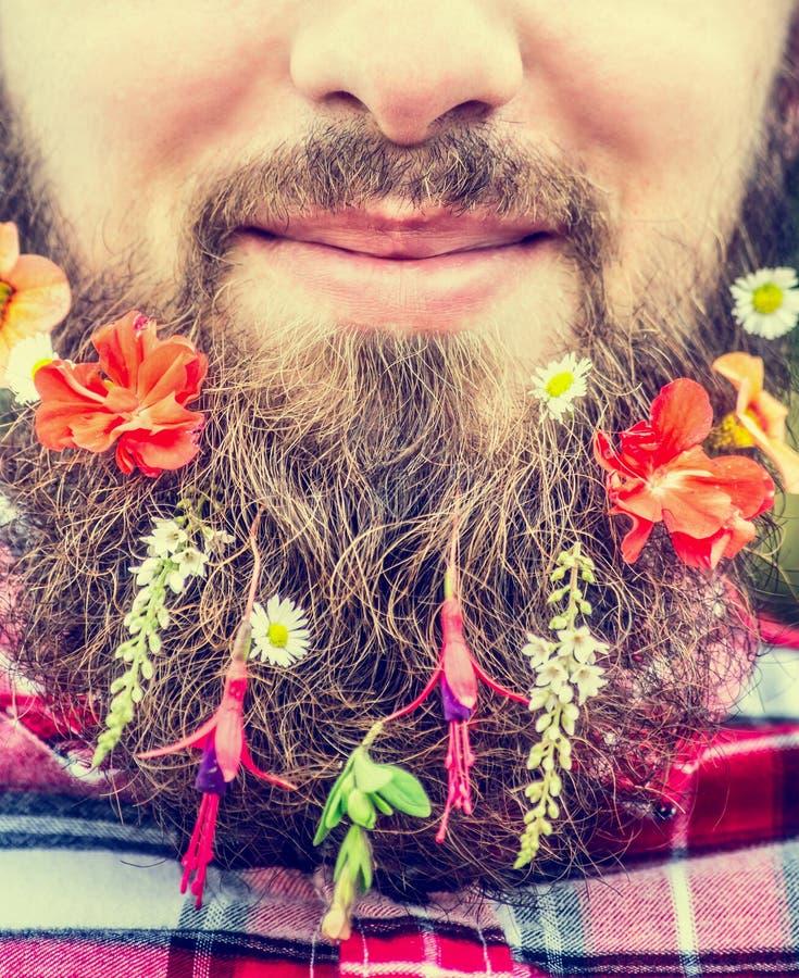 Das Gesicht des Mannes ein langer Bart und Blumen in seinem Bartabschluß oben stockbilder