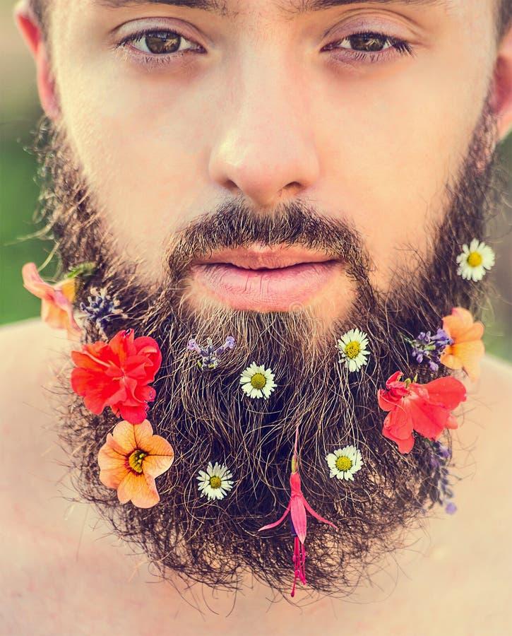 Das Gesicht des Mannes mit einem Bart mit Blumen in seinem natürlicher Hintergrund des Bartes, Abschluss oben stockfotos