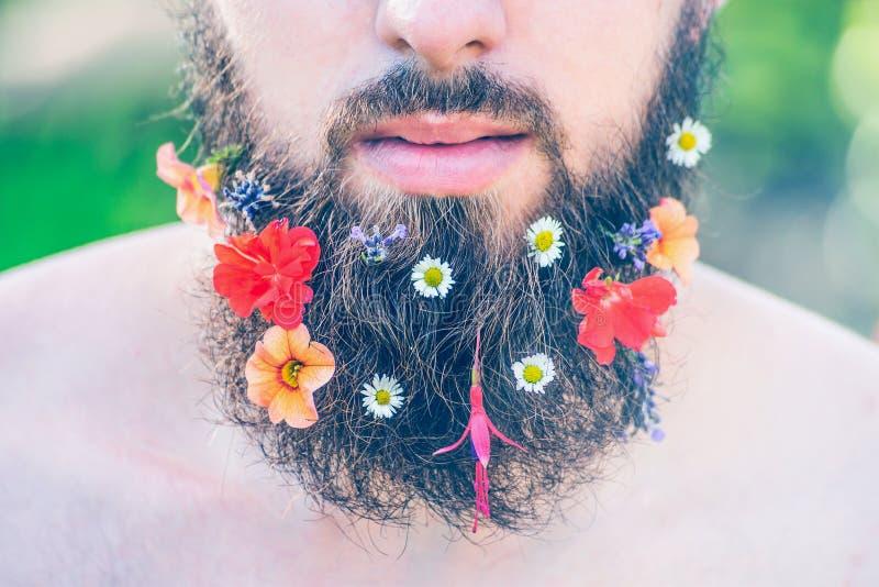 Das Gesicht des Mannes mit einem Bart mit Blumen in seiner Bartnahaufnahme auf dem grünen natürlichen Hintergrund, getont stockbild