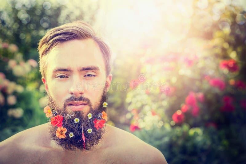 Das Gesicht des stilvollen Mannes mit einem Bart mit Blumen in seinem Bart auf natürlichem hell-farbigem Hintergrund stockfotos