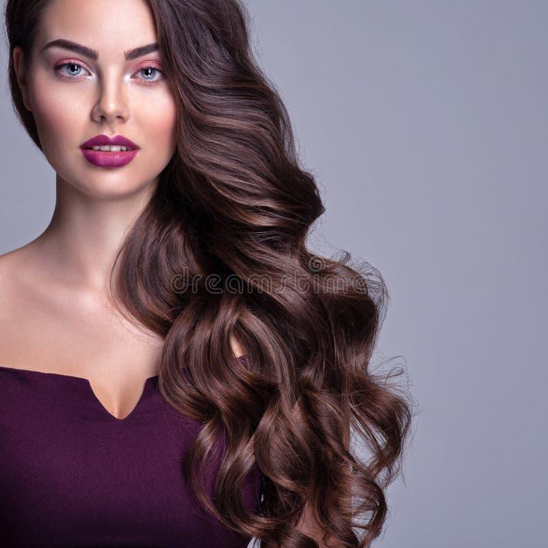 Das Gesicht einer schönen Frau mit langbraunem, lockerem Haar Modemodell mit massiver Frisur Attraktives junges Mädchen mit locke lizenzfreies stockfoto