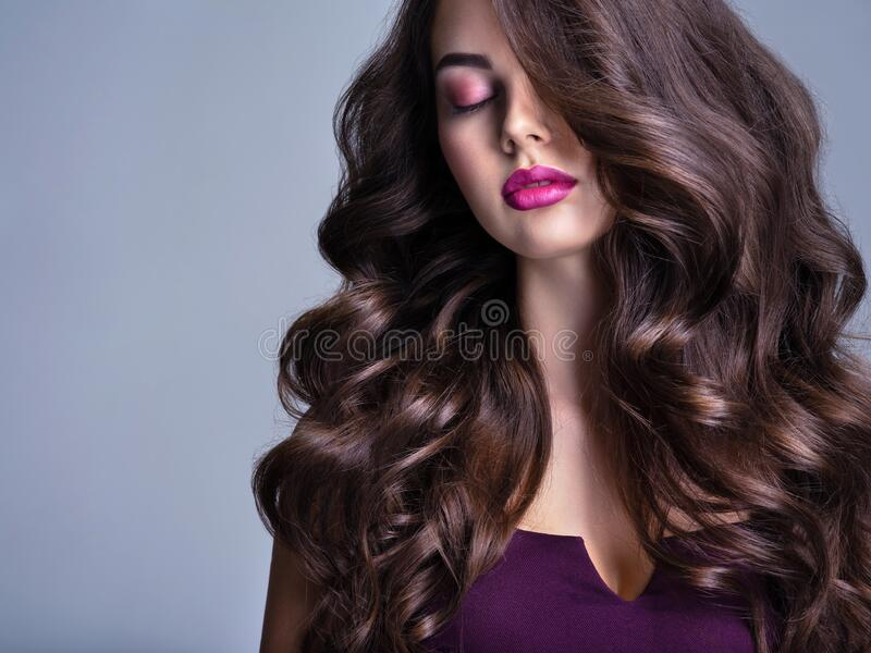 Das Gesicht einer schönen Frau mit langbraunem, lockerem Haar Modemodell mit massiver Frisur Attraktives junges Mädchen mit locke lizenzfreie stockbilder