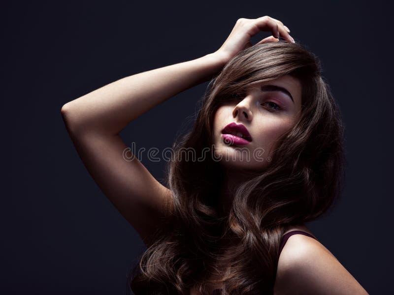 Das Gesicht einer schönen Frau mit langbraunem, lockerem Haar Modemodell mit massiver Frisur Attraktives junges Mädchen mit locke stockfoto