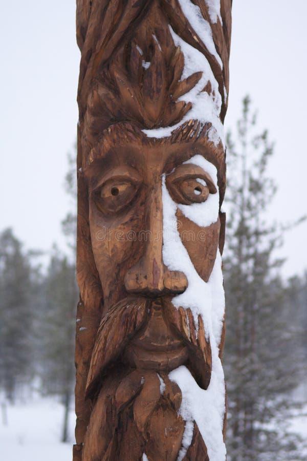 Das Gesicht eines Sami-Idols schnitzte auf einem hölzernen Pfosten stockfoto