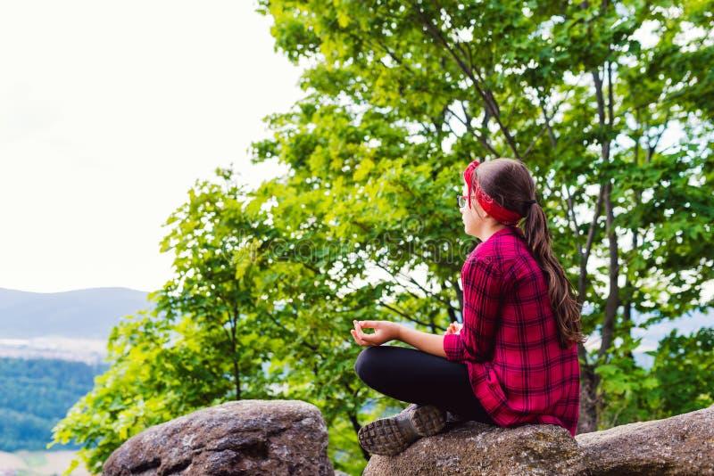 Das gesunde junge Wanderermädchen, das auf Berg in der Yogahaltung sich entspannt, heilen stockbilder
